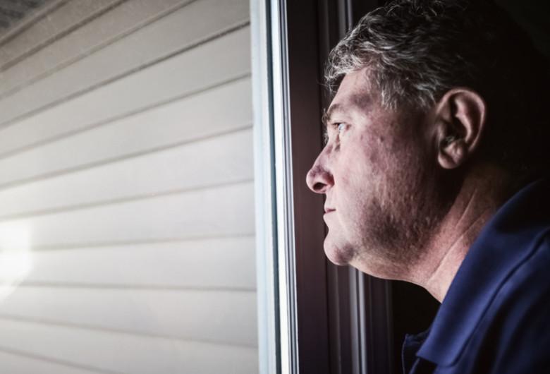 Bărbat trist, deprimat, tulburare psihică, la ușă, privește în gol, asistat social, amărât