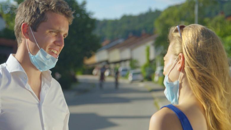 Doi tineri, bărbat și femeie, vorbesc fără mască de protecție împotriva COVID-19, coronavirus, SARS-CoV-2, risc de transmitere a infecției