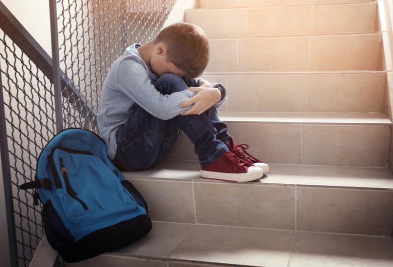 Elev pe scări, la școală, bătut, agresat, bullying, violență, copil cu ghiozdan