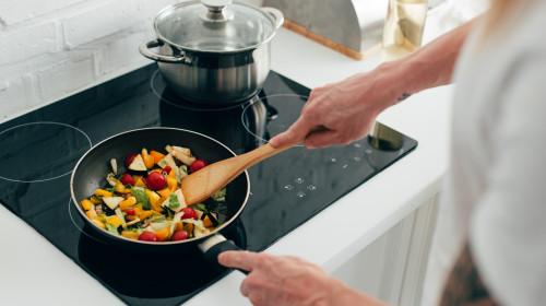 Gătește mâncare sănătoasă cu legume crude, vegetarian, organic în tigaie, pe plită cu inducție, aragaz, hrană în bucătărie