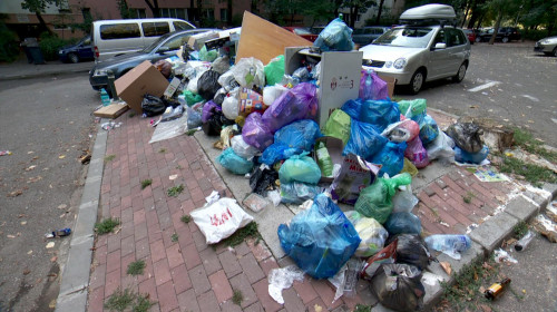 Gunoaie și deșeuri aruncate într-o parcare, pe stradă, poluare, saci cu resturi menajere
