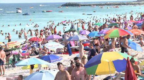 Aglomerație de oameni înghesuiți la mare pe litoral unde fac plajă în Marea Neagră