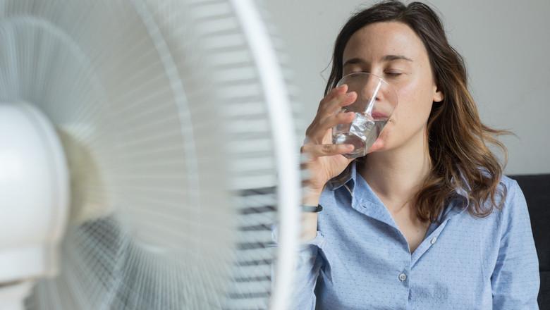 Femeie se răcorește cu apă și ventilator de vremea extrem de caldă cu caniculă și temperaturi ridicate