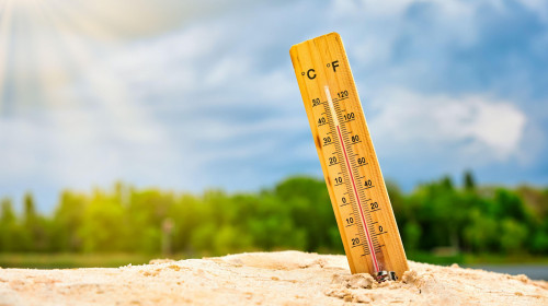 Weather thermometer in the sand against the sky showing a high ambient temperature