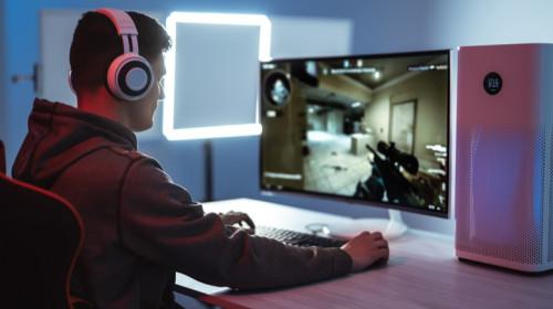 Tânăr joacă Counter-Strike pe calculator de esports cu purificator de aer lângă el