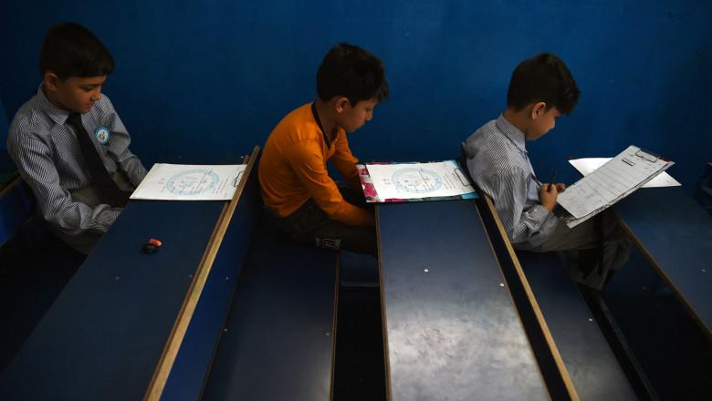 Elevi afgani în școală de educație cu învățământ primar în bănci