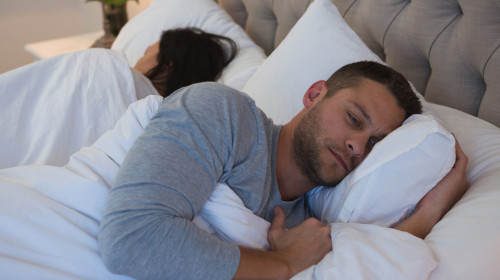 Angry couple avoiding each other in bedroom at home