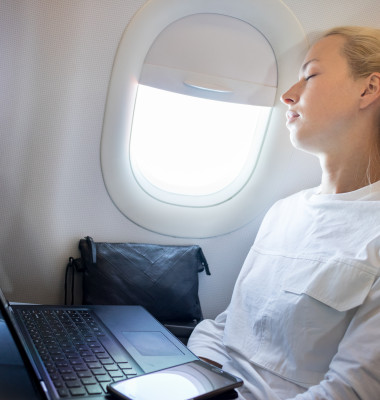 Tired,Business,Woman,Napping,On,Airplane,During,Her,Business,Trip