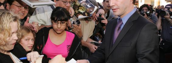 keanu reeves imbracat in costum ofera autografe fanilor