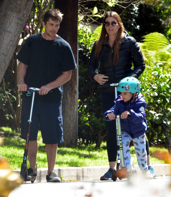 EXCLUSIVE: Actor Christian Bale And His Wife Sibi Are Seen In Their Brentwood, CA Neighborhood On Razor Scooters With Their Young Son Joseph During The Los Angeles Coronavirus Lockdown