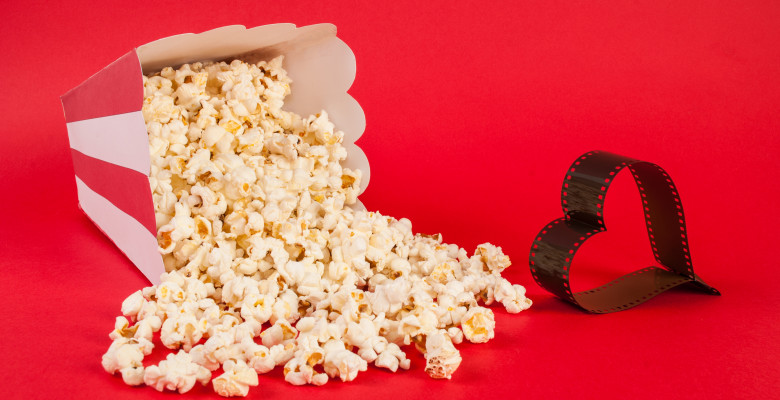 Popcorn,Spilled,On,Blue,Background,And,Film,In,Heart,Form