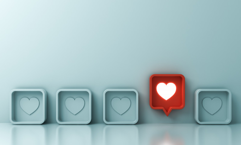 One red social media notification love like heart pin icon pop up from others on light green pastel color wall background Stand out from the crowd and different creative idea concepts