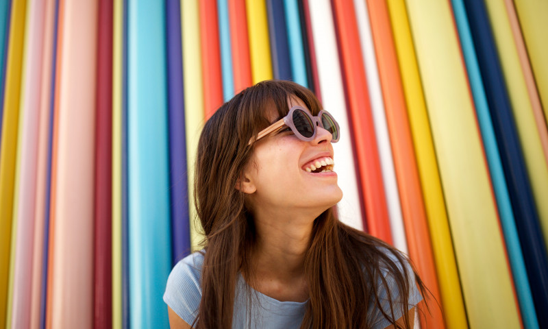 Close up cheerful young woman laughing with sunglasses against colourful background