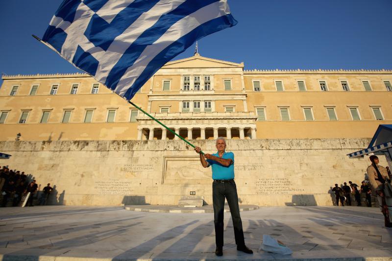 grecia om cu steag in fata parlamentului 1007GettyImages-480064338