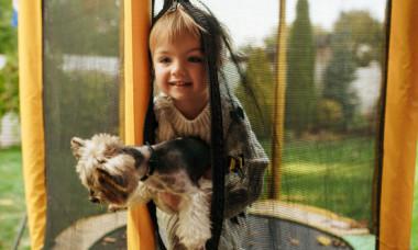 Momentul adorabil în care o fetiță și câinele ei sar pe trambulină: