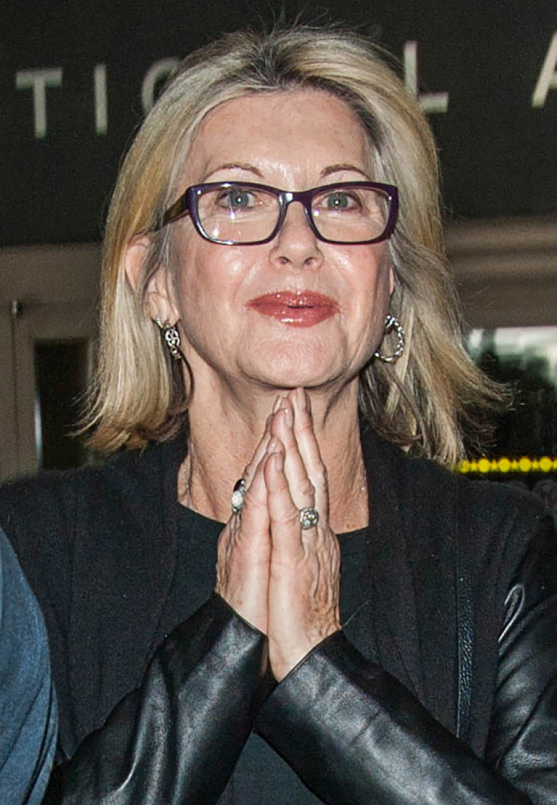 Olivia Newton John is all smiles in black leather at LAX airport
