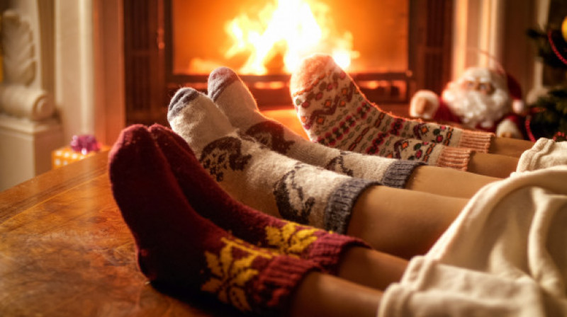 Closeup photo of family feet in woolen socks lying next to fireplace