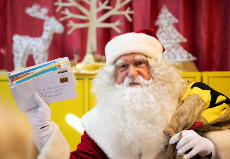 Moş Crăciun ţine în mână scrisori venite de la copii